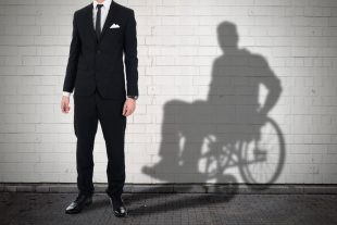 A man in standing in front of a white wall, his shadow behind him shows him sitting down in a wheelchair.