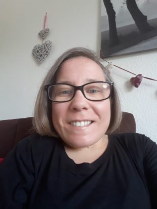 Donna is wearing a black top and glasses and is smiling at the camera.