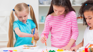 Three young girls paint together at a table, one has a visible disability.