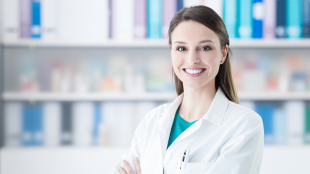 A healthcare professional is smiling at the camera with her arms crossed. She is standing in front of a bookshelf in a clinical setting.