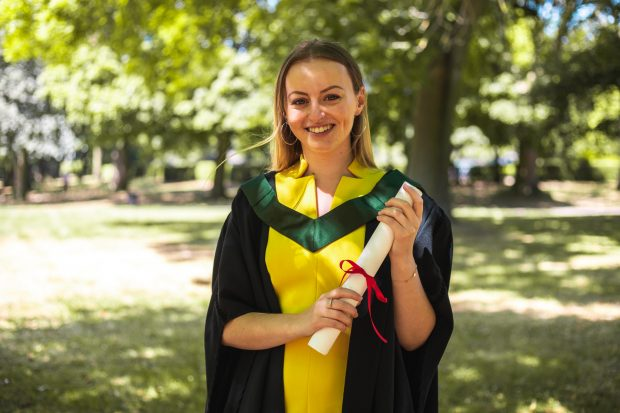 Eleanor is standing outside at her graduation, wearing a yellow dress and dark green and black graduation robes. She is holding a degree scroll and smiling.