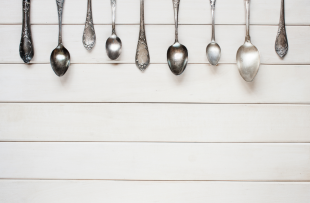 The image shows a row of metal spoons across the top of the frame on a table. The background is a light grey colour.