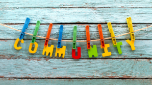 Plastic letters spelling out 'community' in primary colours and pegged onto a washing line.