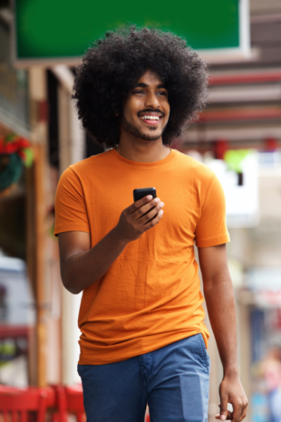 A black man smiles as he walks down the street, he has his phone held up in front of him as if he is texting.