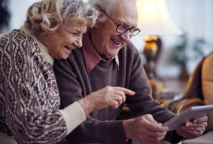 An elderly man and woman smile while looking at a tablet.